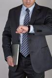 Hombre de negocios joven que mira su reloj que comprueba el tiempo Imagen de archivo libre de regalías