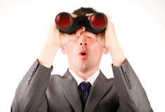 Hombre de negocios joven que mira a través de los prismáticos Fotos de archivo libres de regalías