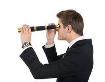 Hombre de negocios joven que mira a través del telescopio del PDA Foto de archivo