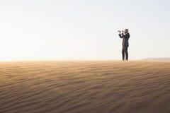 Hombre de negocios joven que mira a través del telescopio en el medio del desierto Fotografía de archivo libre de regalías