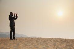 Hombre de negocios joven que mira a través del telescopio en el medio del desierto Imagen de archivo libre de regalías