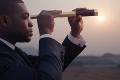 Hombre de negocios joven que mira a través del telescopio en el medio del desierto Imagen de archivo