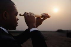 Hombre de negocios joven que mira a través del telescopio en el medio del desierto Fotos de archivo
