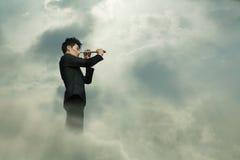 Hombre de negocios joven que mira a través del telescopio en una nube dreamlike Fotos de archivo libres de regalías