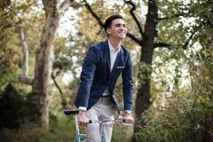 Hombre de negocios joven que monta una bicicleta al aire libre en parque imagen de archivo