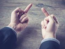 Hombre de negocios joven que muestra el dedo medio que gesticula cogida usted, concepto sobre el negocio enojado o furioso, color Fotos de archivo