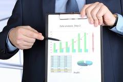 Hombre de negocios joven que muestra gráficos por la pluma Foto de archivo libre de regalías
