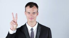 Hombre de negocios joven que muestra la muestra de la victoria almacen de metraje de vídeo