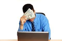 Hombre de negocios joven que piensa con el dinero Fotografía de archivo