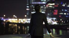 Hombre de negocios joven que pone en los vidrios y que mira un paisaje urbano la noche almacen de metraje de vídeo