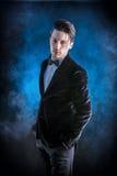 Hombre de negocios joven que presenta con confianza en fondo oscuro Foto de archivo libre de regalías