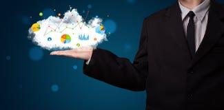 Hombre de negocios joven que presenta la nube con las cartas y los iconos a del gráfico Fotos de archivo libres de regalías