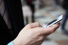 Hombre de negocios joven que pulsa con el teléfono celular imágenes de archivo libres de regalías