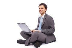 Hombre de negocios joven que pulsa en una computadora portátil Fotos de archivo libres de regalías