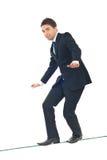 Hombre de negocios joven que recorre en cuerda de volatinero Foto de archivo libre de regalías