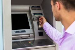 Hombre de negocios joven que retira el dinero de un cajero automático imagen de archivo