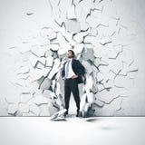 Hombre de negocios joven que rompe el canal una pared Fotografía de archivo
