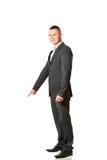 Hombre de negocios joven que señala abajo Imagenes de archivo