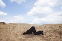 Hombre de negocios joven que se arrodilla con su cabeza en un agujero en la arena Fotografía de archivo libre de regalías