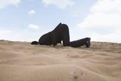 Hombre de negocios joven que se arrodilla con su cabeza en un agujero en la arena Fotografía de archivo