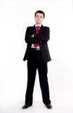 Hombre de negocios joven que se coloca con los brazos cruzados imagenes de archivo