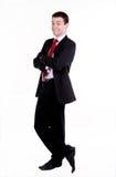Hombre de negocios joven que se coloca con los brazos cruzados foto de archivo