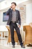 Hombre de negocios joven que se coloca en oficina y que habla en el teléfono Imagen de archivo libre de regalías