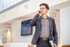 Hombre de negocios joven que se coloca en oficina y que habla en el teléfono Foto de archivo libre de regalías