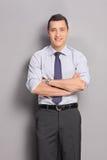 Hombre de negocios joven que se inclina contra una pared gris Fotos de archivo