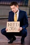 Hombre de negocios joven que se pone en cuclillas con trabajo de la necesidad de la muestra fotos de archivo libres de regalías