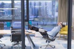 Hombre de negocios joven que se relaja en el escritorio Imágenes de archivo libres de regalías