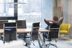Hombre de negocios joven que se relaja en el escritorio Fotos de archivo