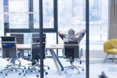 Hombre de negocios joven que se relaja en el escritorio Fotografía de archivo