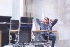 Hombre de negocios joven que se relaja en el escritorio Fotografía de archivo libre de regalías