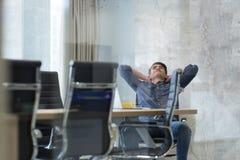 Hombre de negocios joven que se relaja en el escritorio Foto de archivo libre de regalías