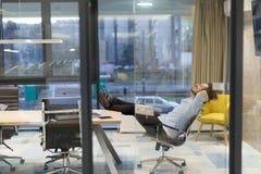 Hombre de negocios joven que se relaja en el escritorio Imagen de archivo