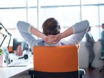 Hombre de negocios joven que se relaja en el escritorio Fotos de archivo libres de regalías