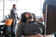 Hombre de negocios joven que se relaja en el escritorio Imagenes de archivo