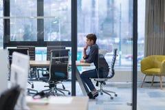 Hombre de negocios joven que se relaja en el escritorio Foto de archivo