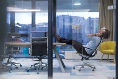 Hombre de negocios joven que se relaja en el escritorio Imagen de archivo libre de regalías