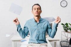 Hombre de negocios joven que se relaja y que medita en la oficina fotografía de archivo libre de regalías