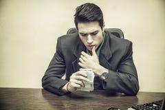 Hombre de negocios joven que se sienta Counting Cash a mano Fotos de archivo