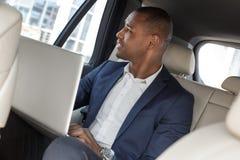 Hombre de negocios joven que se sienta en asiento trasero en el funcionamiento del coche en el ordenador portátil que mira hacia  imagen de archivo