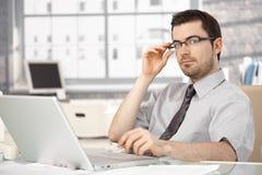 Hombre de negocios joven que se sienta en el escritorio usando la computadora portátil Imágenes de archivo libres de regalías
