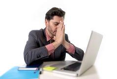 Hombre de negocios joven que se sienta en el funcionamiento de escritorio de oficina en preocupante desesperado del ordenador por Foto de archivo