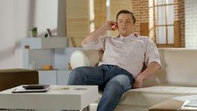 Hombre de negocios joven que se sienta en el sofá, teniendo conversación telefónica con el socio fotografía de archivo libre de regalías