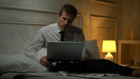 Hombre de negocios joven que se sienta en la cama que hace los movimientos de baile ligeros, inicio acertado metrajes