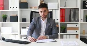 Hombre de negocios joven que se sienta en la tabla en la oficina blanca y que mira cuidadosamente la cámara