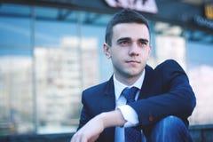 Hombre de negocios joven que se sienta en los pasos de la oficina Imagen de archivo