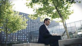 Hombre de negocios joven que se sienta en un parque cerca de oficina y que usa el ordenador portátil